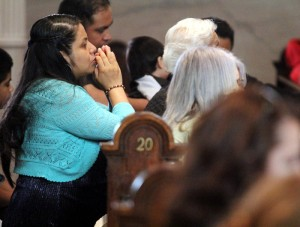 Maria Alameda prays with her family during the Spanish mass at St. Michael Church.