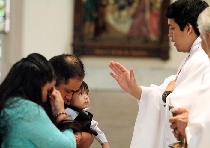 Father Arturo Chagala offer a blessing for Pablo Perez on his first birthday at the end of mass.
