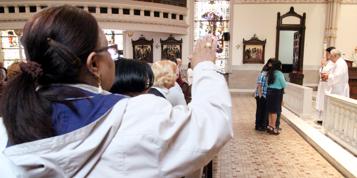 The spanish community at St. Michael Church extend their hands to offer a blessing to Pablo Perez on his first birthday.