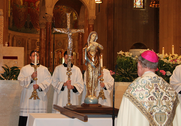 Bishop Michael Fitzgerald prays before the corwning of a statue of Mary April 23 at the Basilica of the Nat