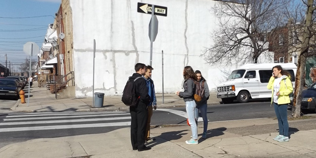 Volunteers of the Legionaries of Christ-led Youth Mission team gather on a Grays Ferry street corner on a day during the recent Holy Week before going door to door in the neighborhood, asking for residents' prayer intentions, for which the group and parishioners prayed during a special liturgy.