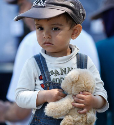 A boy holds his teddy bear as Pope Francis leads a meeting with refugees at the Moria refugee camp on the island of Lesbos, Greece, April 16. (CNS photo/Paul Haring)