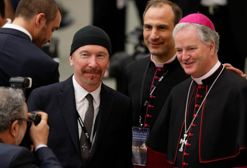 U2 guitarist David Evans, also known by his stage name The Edge, poses with Msgr. Melchor Jose Sanchez de Toca y Alameda, under secretary of the Pontifical Council for Culture, and Irish Bishop Paul Tighe, adjunct secretary of the same council, during a conference on adult stem cell research at the Vatican April 29. (CNS photo/Paul Haring)