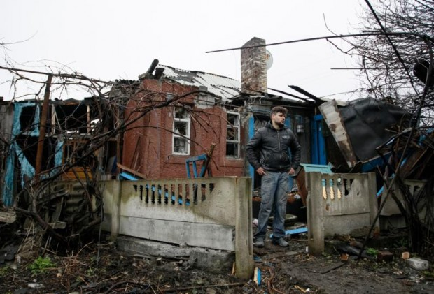 A man stands in front his damaged house after shelling March 24 in the Ukrainian town of Makeevka. (CNS photo/Alexander Ermochenko, EPA)