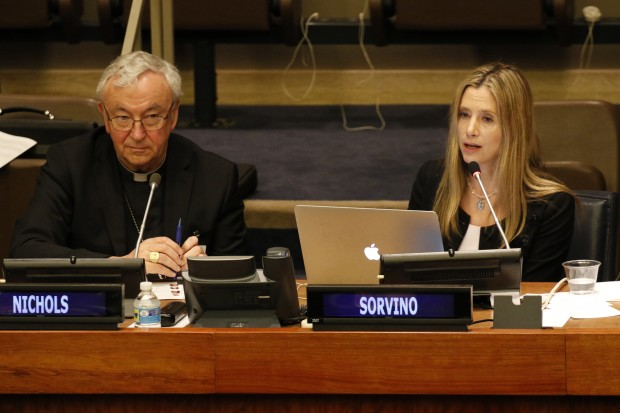 Actress Mira Sorvino, a U.N. goodwill ambassador for the global fight against human trafficking, addresses the audience during a conference on human trafficking April 7 at the United Nations in New York City. Looking on is Cardinal Vincent Nichols of Westminster, England. (CNS photo/Gregory A. Shemitz)