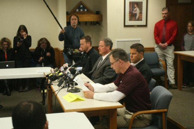 Principal Tom Zamzow of Antigo High School in Wisconsin, reads a statement during a press conference at Antigo City Hall April 25. The community is coping with a shooting at Antigo High School April 23 that left one young man dead adn two students injured. Also pictured are Brian Misfeldt, left, school district administrator-designate; Langlade County Sheriff Bill Greening and Antigo Police Chief Eric Roller. (CNS photo/Lisa Haefs, for The Compass)