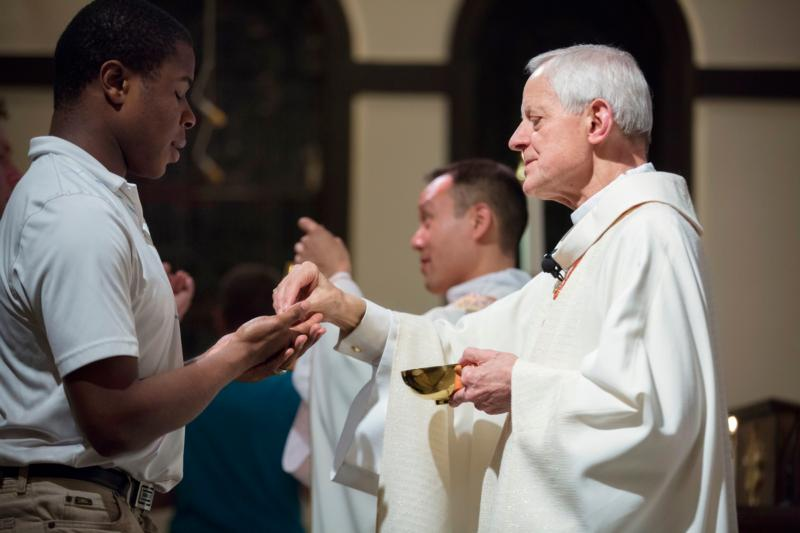 Cardinal Donald W. Wuerl of Washington gives Communion to a young man during the April 21 University Mass for Life at Epiphany Catholic Church in Washington. (CNS photo/Jaclyn Lippelmann, Catholic Standard)