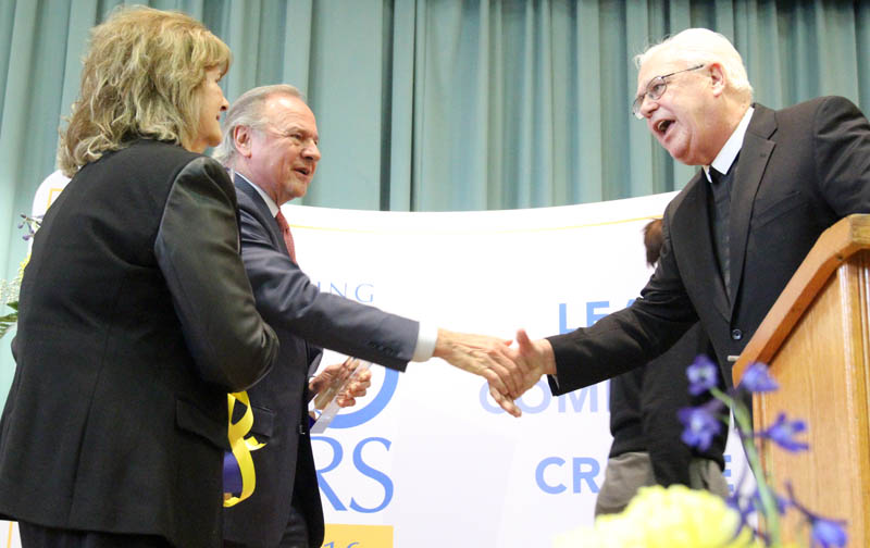 West Catholic Preparatory High School President  Brother Richard Kestler, F.S.C. (right), shows his gratitude for Helen and Leonard Mazur's $5 million gift at the school April 28. (Photo by Sarah Webb)