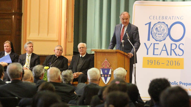 Leonard Mazur speaks to the student body of West Catholic Preparatory High School, which is celebrating its 100th anniversary this year, while looking on are (from left): Sister Maureen McDermott, I.H.M., archdiocesan superintendent of secondary schools; Casey Carter, CEO of Faith in the Future Foundation; Archbishop Charles Chaput; and Brother Richard Kestler, F.S.C., school president. (Sarah Webb)