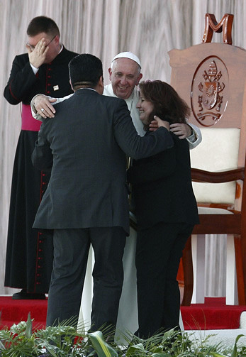 "Pope Francis embraces Humberto and Claudia Gomez, who are married civilly but not in the church, during a meeting with families at the Victor Manuel Reyna Stadium in Tuxtla Gutierrez, Mexico, Feb. 15. Pope Francis' postsynodal apostolic exhortation on the family, ""Amoris Laetitia"" (""The Joy of Love""), was released April 8. (CNS photo/Paul Haring)"