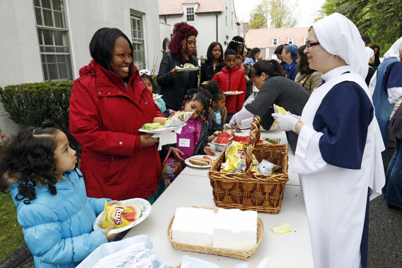 Sister Celeste Marie, a novice with the Sisters of Life, helps distribute food to guests during the annual Mother's Day celebration May 8 at the religious community's retreat house in Stamford, Conn. (CNS photo/Gregory A. Shemitz)