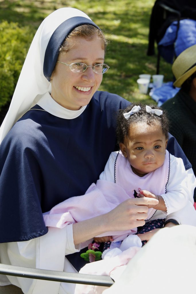 Sister Talitha Guadalupe, a member of the Sisters of Life, holds six-month-old Esther during the annual Mother's Day celebration May 8 at the religious community's retreat house in Stamford, Conn. (CNS photo/Gregory A. Shemitz)