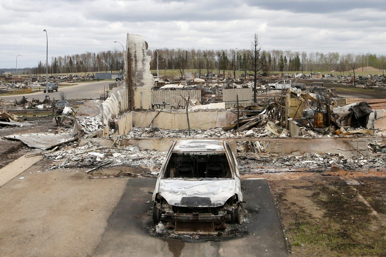 A charred vehicle and home are pictured in the burned-out Beacon Hill neighborhood of Fort McMurray, Alberta, May 9, after wildfires forced the evacuation of the entire town. (CNS photo/Chris Wattie, Reuters)