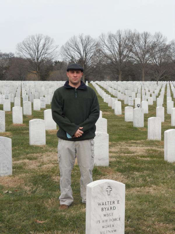 Father Joseph Brankatelli stands among graves in Arlington National Cemetery in Virginia in late February.(CNS photo/Jerri Donohue)