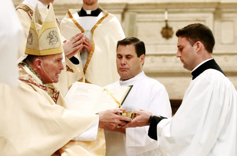 Kyle Adamczyk (right), a Second Theology seminarian studying for the Philadelphia Archdiocese, receives the ministry of acolyte from Bishop David O'Connell.