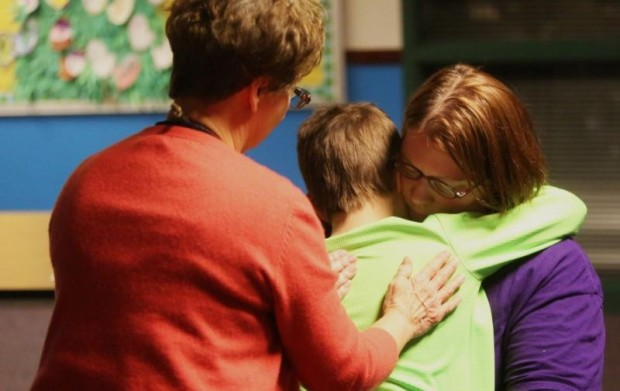 Bonnie Serio, a pastoral care specialist, comforts 8-year-old Max as he hugs his mother, Debbie Gonsioroski, right, during a March 3 session of Partners Around Loss through Support, or PALS, at Faithful Shepherd Catholic School in Eagan, Minn. (CNS photo/Dave Hrbacek, The Catholic Spirit)