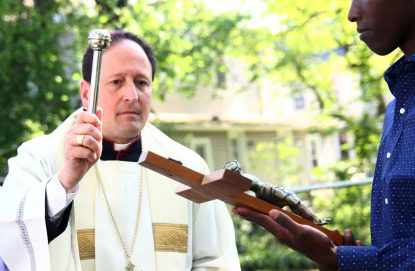 Bishop John McIntyre blesses a crucifix for Blessed Oscar Romero House May 11 in Bensalem. Sarah Webb)