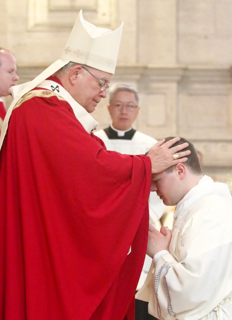 Archbishop Charles Chaput lays his hands on Matthew Brody, ordaining him a transitional deacon.