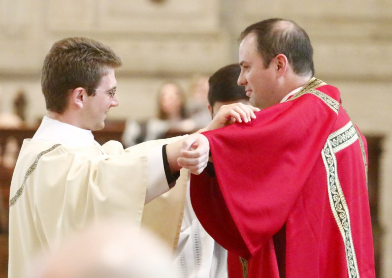 Brian Connolly wears the dalmatic, the liturgical vestment of a deacon, for the first time with the assistance of Deacon Matthew Biedrzycki.