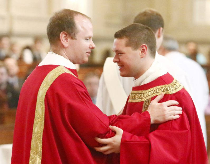 Deacons Matthew Windle and Matthew Brody exchange a sign of peace.