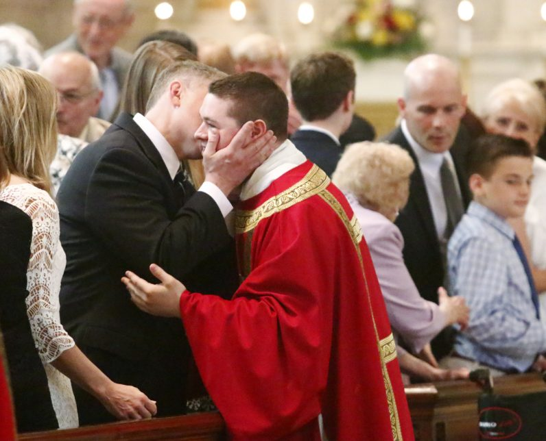 Deacon Matthew Brody and his father offer one another a kiss of peace.
