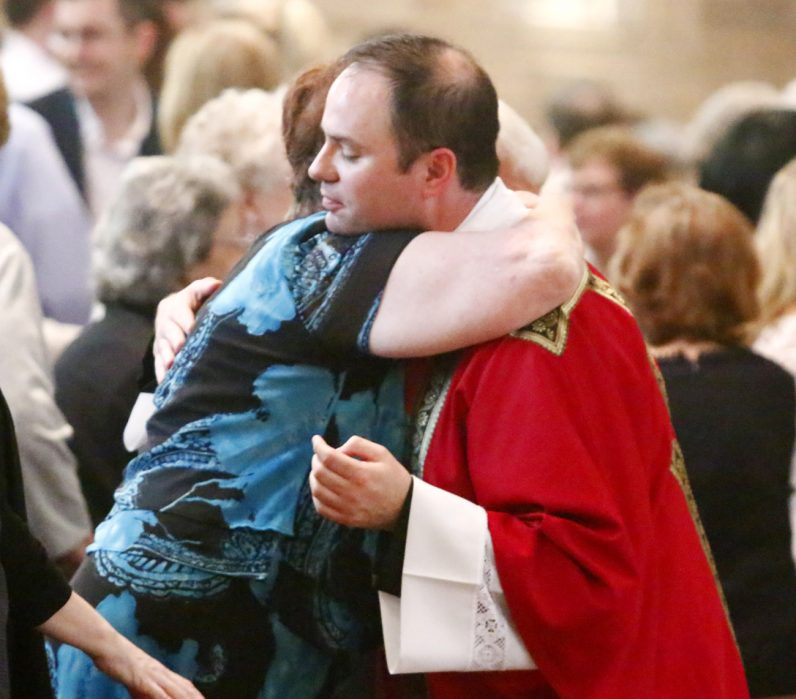 Deacon Brian Connolly exchanges a sign of peace with his mother.