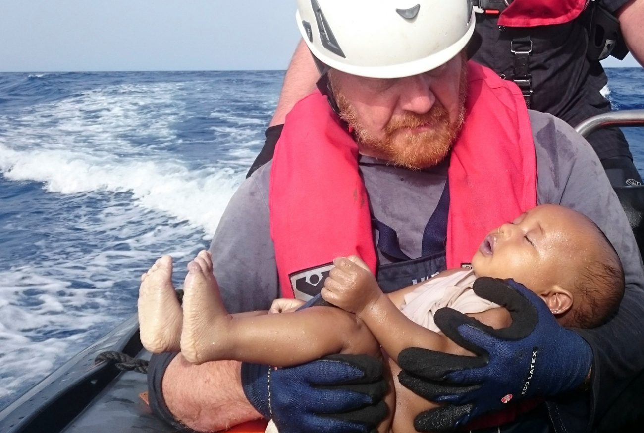 A German rescuer from the humanitarian organization Sea-Watch holds a migrant baby May 27 who drowned off the Libyan cost. The baby, who appears to be no more than a year old, was pulled from the sea after a wooden boat capsized. (CNS photo/Christian Buettner, Eikon Nord GmbH Germany Handout via Reuters)