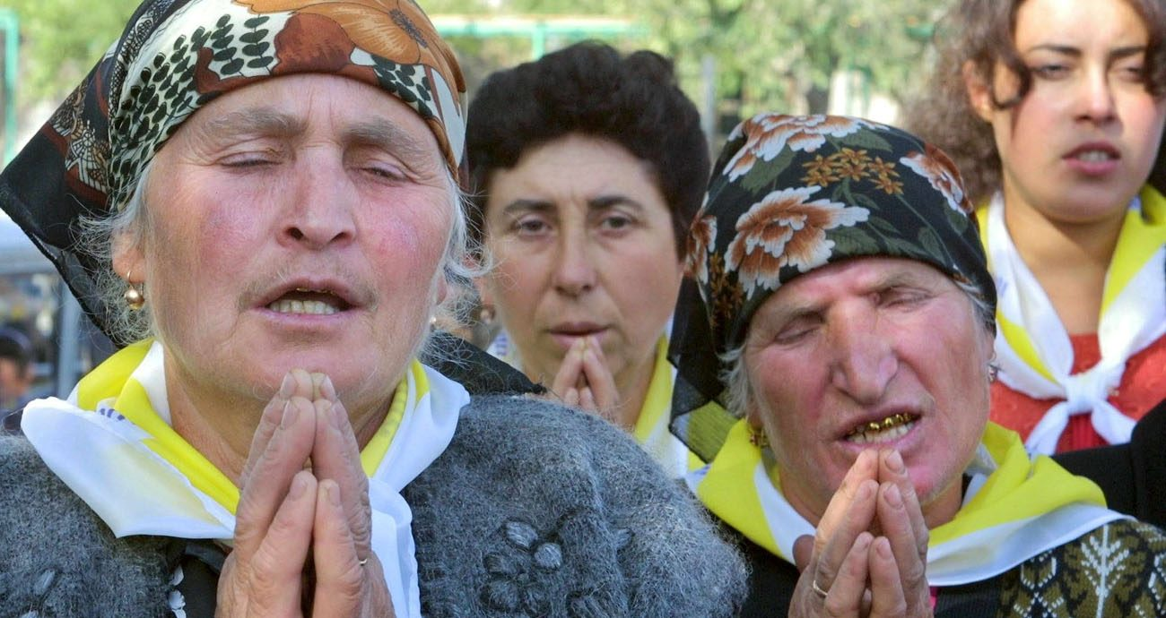 "Armenian women pray during a 2001 Mass celebrated by St.  John Paul II at Echmiadzin, in Vagharshapat, Armenia. Many Armenians said Pope Francis will be widely welcomed when he visits Armenia in June 24-26, thanks in part to a remark he made more than a year ago in which he referred to the forced evacuation of Armenians by Ottoman Turks as ""genocide."" (CNS photo/Sergei Supinsky, EPA)"