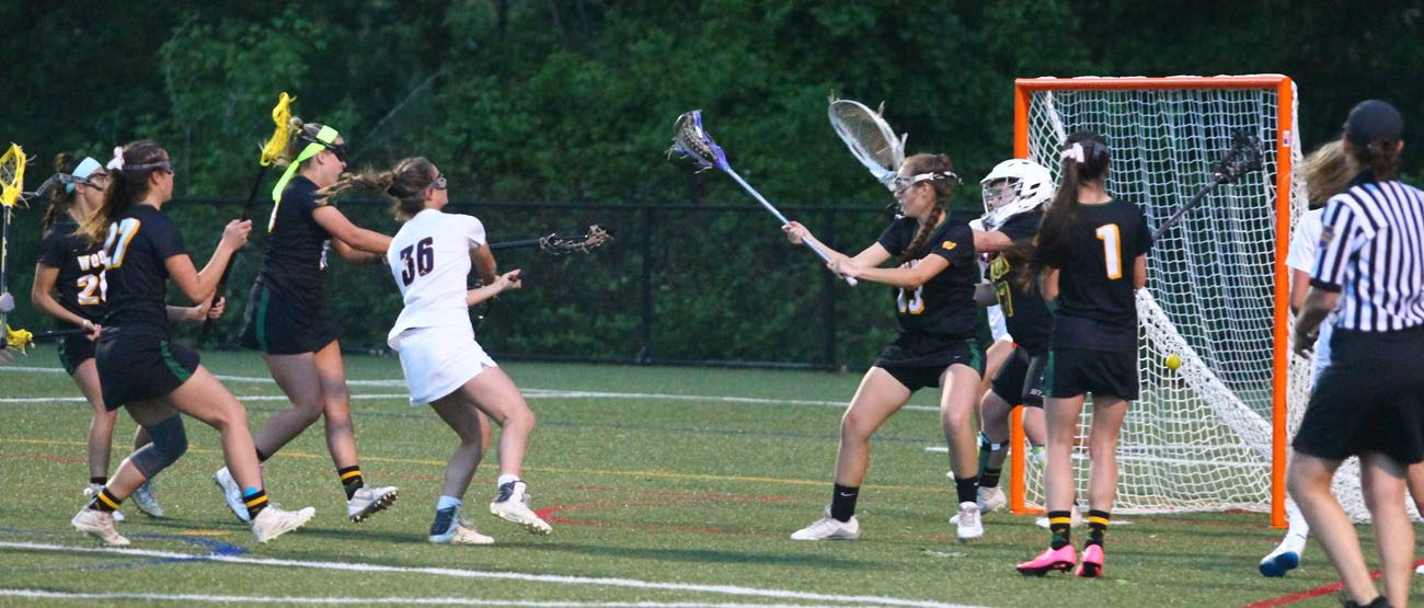 Even against a phalanx of defenders, an Archbishop Carroll player makes her way to the goal in the Catholic League championship game May 23. (D'Mont Reese)