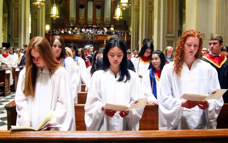 Young ladies from Academy of Notre Dame de Namur sing along during the honors convocation liturgy.