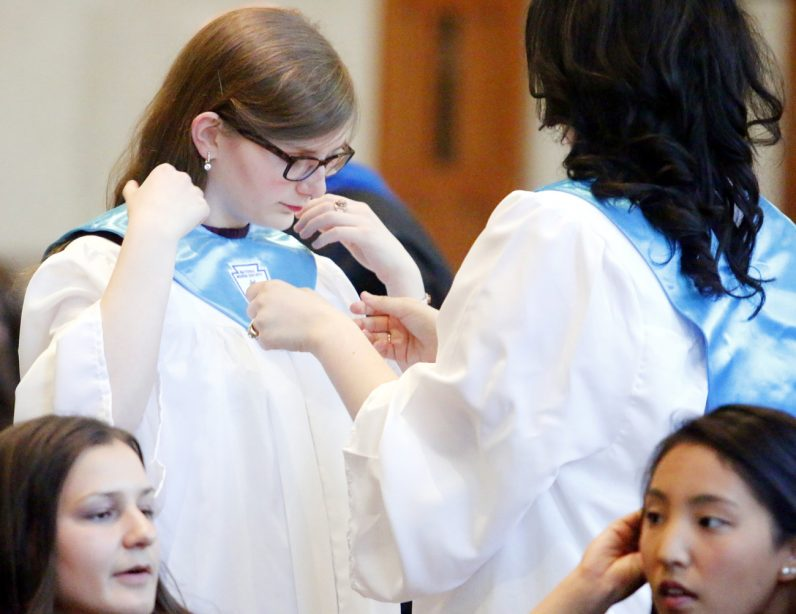 Little Flower High School graduate Theresa Pearce (right) helps Jamie Galanaugh straighten her gown.
