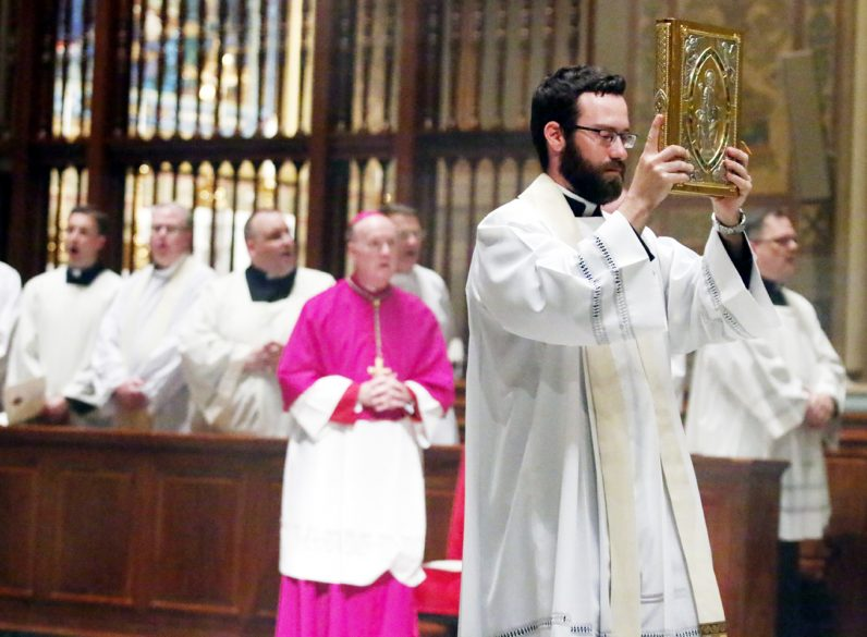 Father Christopher Landis processes with the book of Gospels for the liturgy's reading.