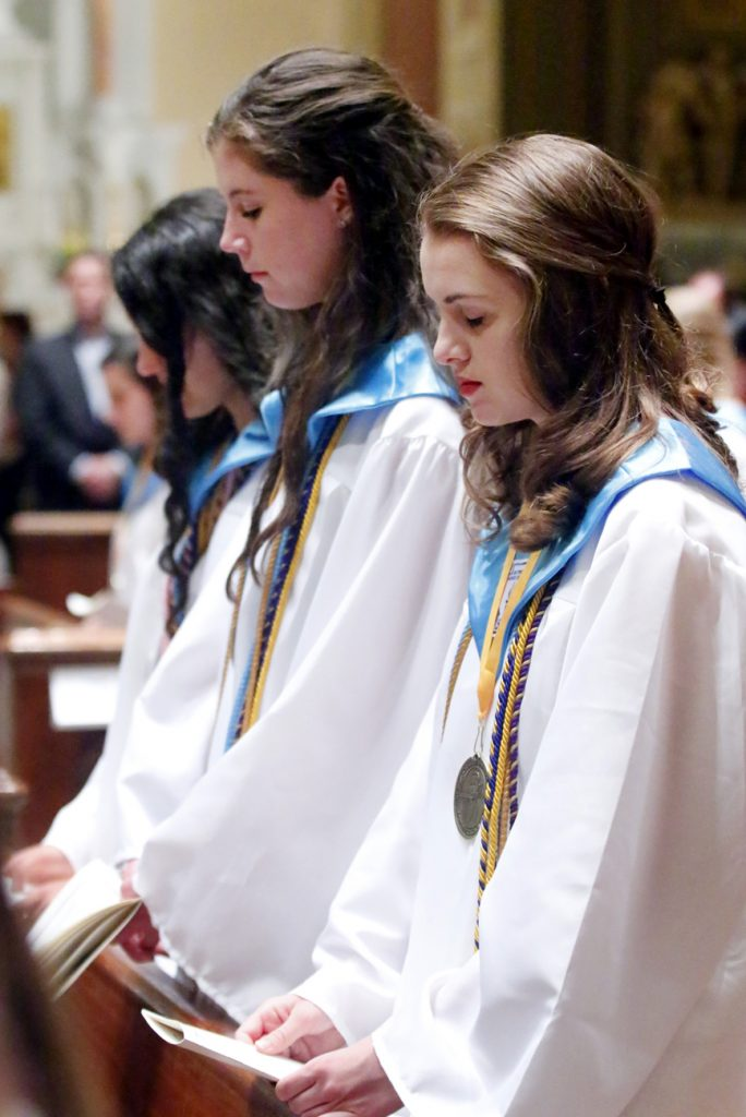 Students from Nazareth Academy bow their heads in prayer.
