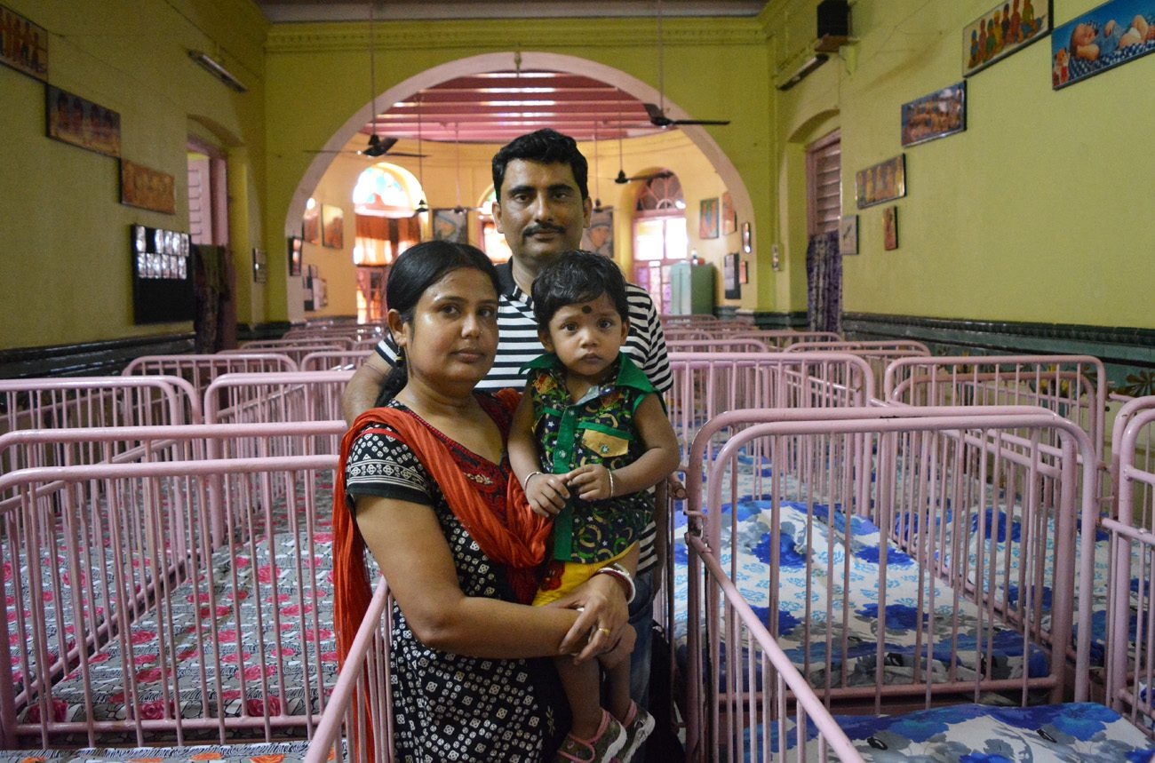 "Anirban Mukherjee (center rear) and his wife, Sampa, pose May 2 with their 17-month-old son Anirban at Shishu Bhavan, the Missionaries of Charity children's home in Kolkata, India. The parents adopted Anirban from the home in April 2015 and call him ""the gift from the saint of Kolkata, Mother Teresa.""  (CNS photo/Saadia Azim)"