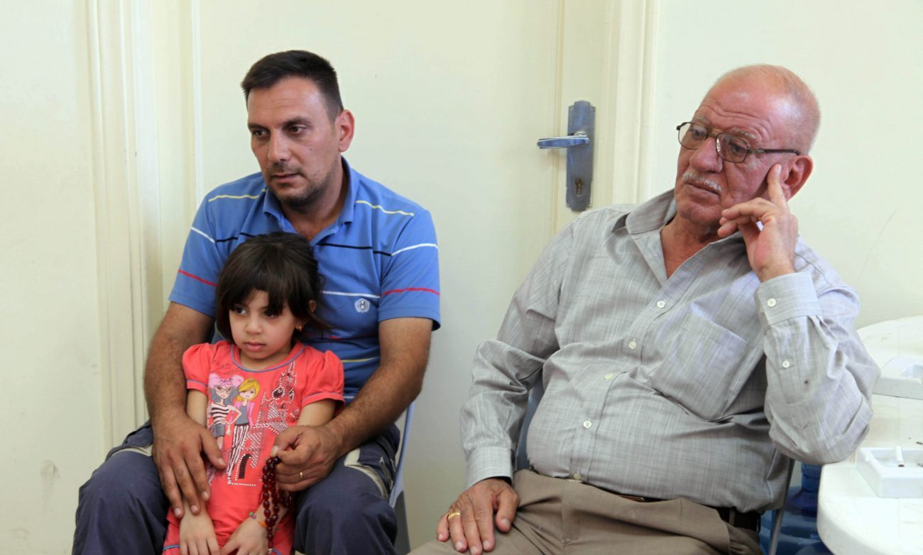A Christian family who fled from violence in Mosul, Iraq, sit in the room of a church in 2014 in Amman, Jordan. The Vatican is funding a job-creation program for Iraqi refugees in Jordan, a country that is hosting close to 1.5 million refugees, but is struggling to provide work for them. (CNS photo/Jamal Nasrallah, EPA)