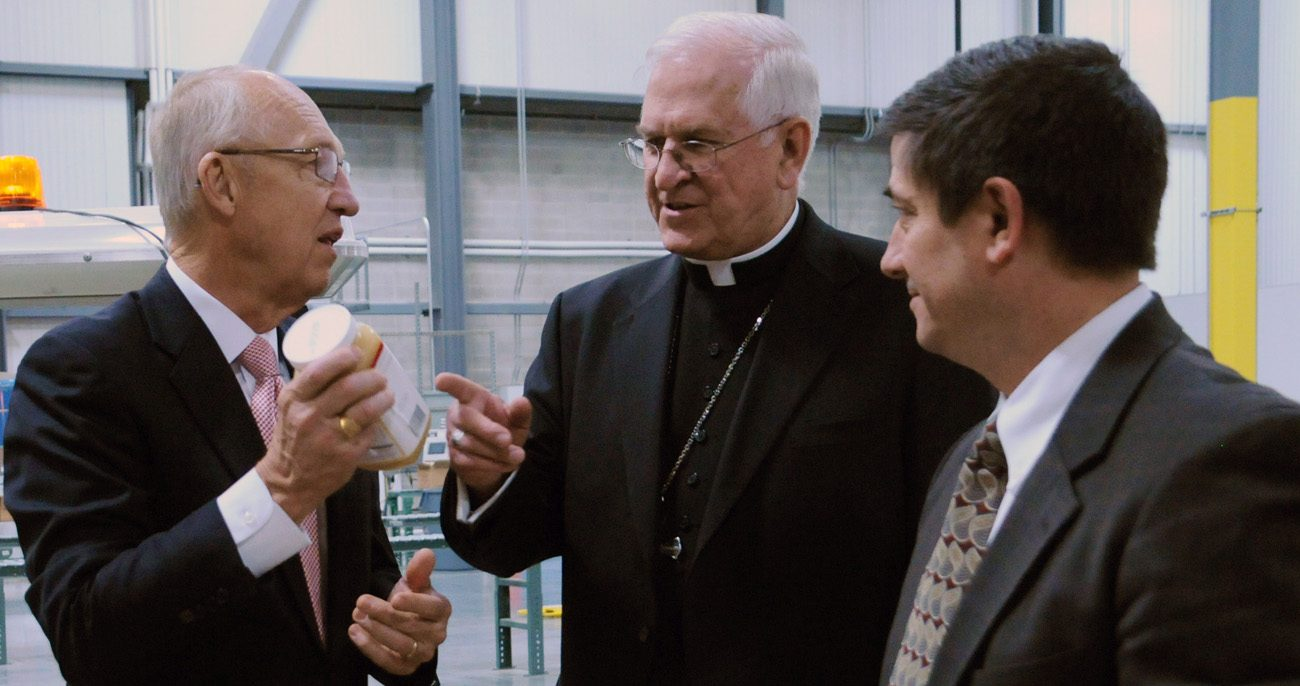 Elder Don R. Clark (left), of the Church of Jesus Christ of Latter-day Saints, explains to Archbishop Joseph E. Kurtz of Louisville, Ky., president of the U.S. Conference of Catholic Bishops, on a visit May 4 to the Central Storehouse that much of the food the LDS Church distributes to the needy has a church label. (CNS photo/Marie Mischel, Intermountain Catholic)