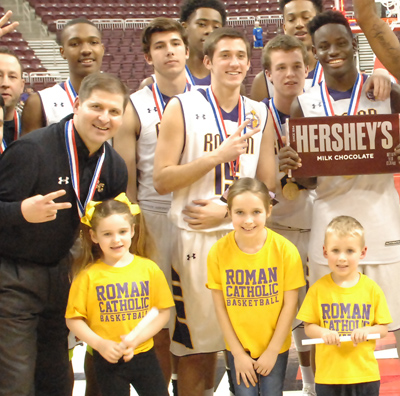 Coach Chris McNesby celebrates his team's PIAA Class AAAA championship along with players and his three young children March 19 in Hershey, Pa.
