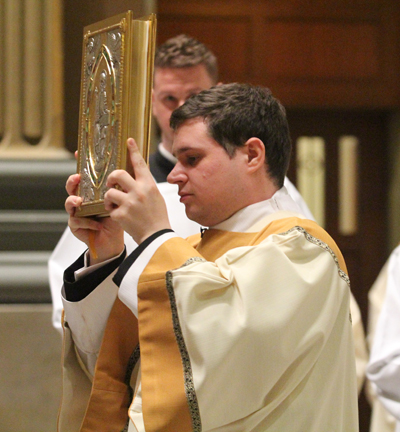 Transitional Deacon Thomas O'Donald carries the book of Gospels in procession during the Mass of the Lord's Supper March 24 in the Cathedral Basilica of SS. Peter and Paul, Philadelphia (Sarah Webb)