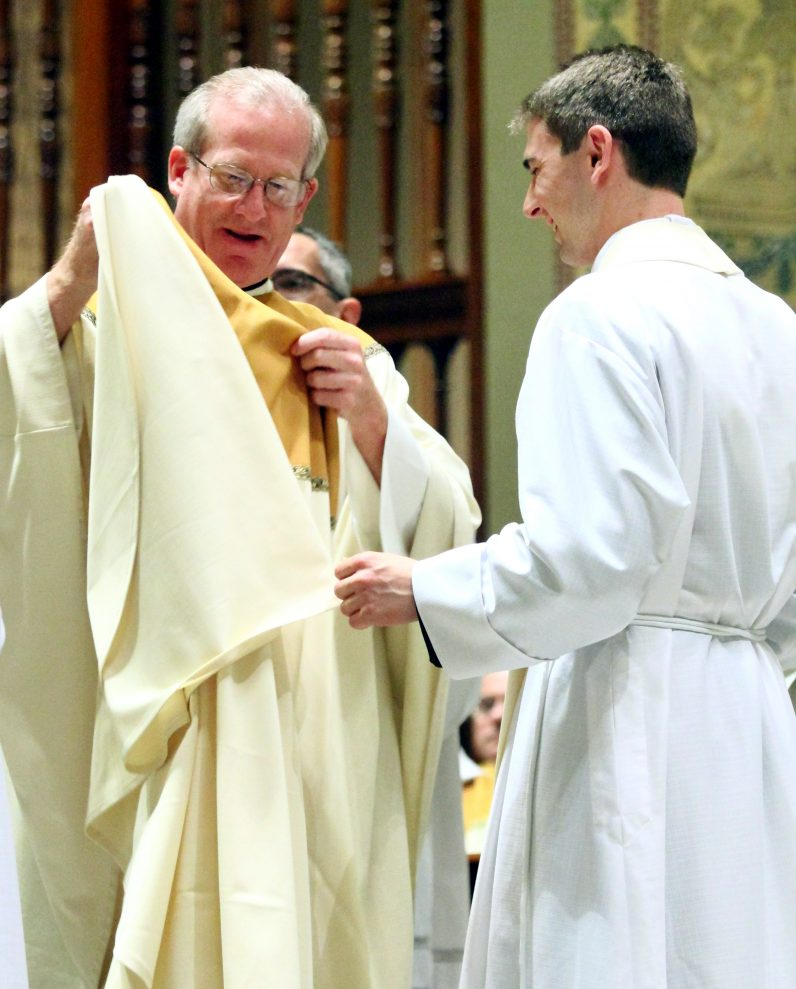 Father Thomas Higgins assists the newly ordained Father Matthew Biedrzycki in vesting for the first time as a priest.