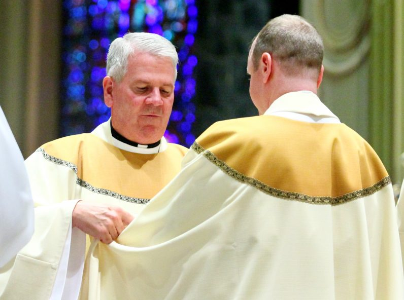 Father Paul Kennedy helps Father Matthew Windle don the vestments of a priest for the first time.