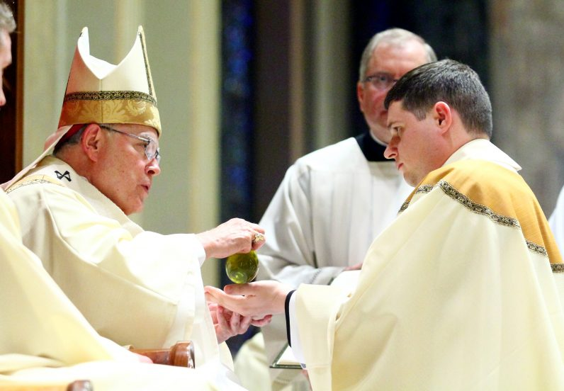 Archbishop Charles Chaput anoints the hands of Father Thomas O'Donald with sacred chrism.