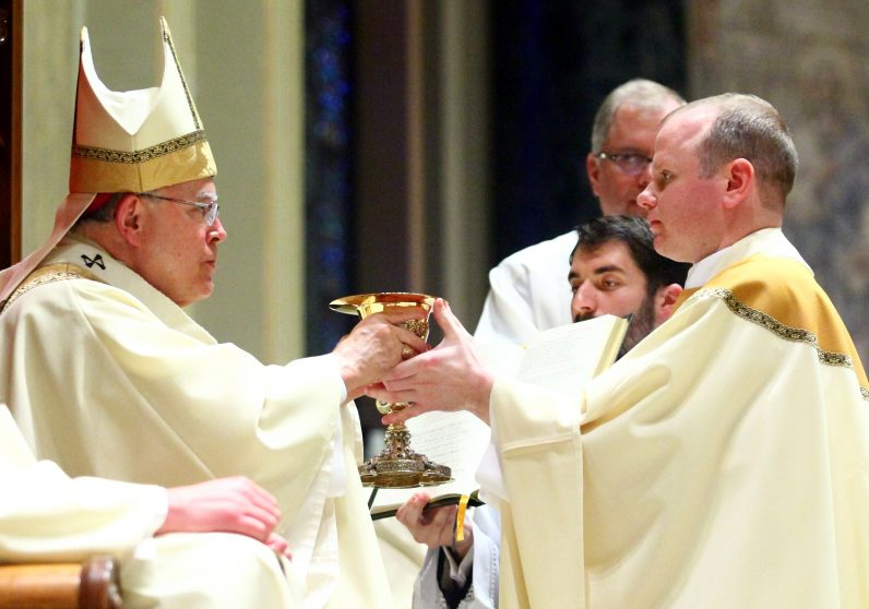 Archbishop Charles Chaput presents the paten and chalice, vessels for holding the bread and wine for the Eucharist, to Father Matthew Windle.