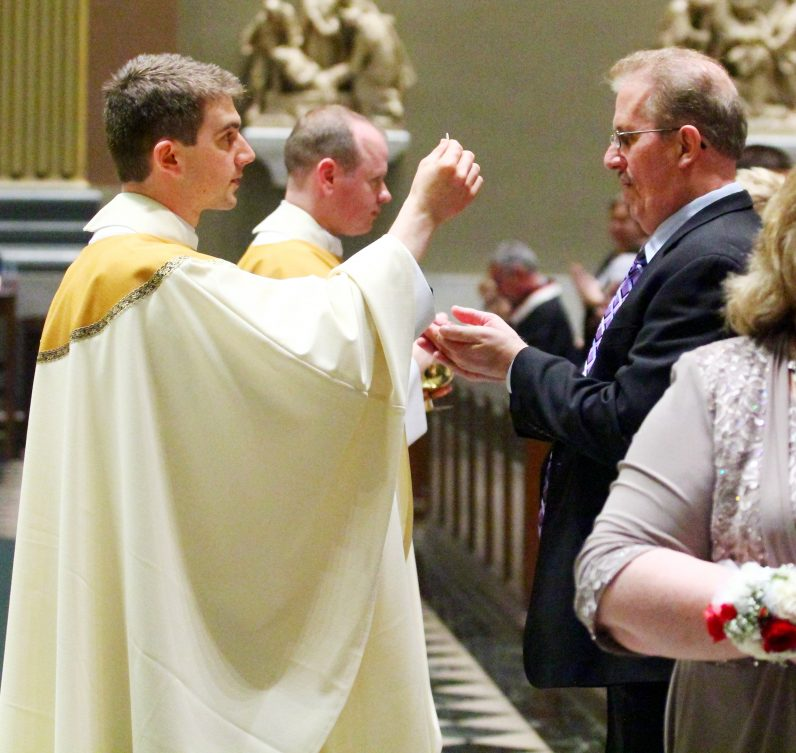 Father Matthew Biedrzycki gives holy Communion to his father, John.