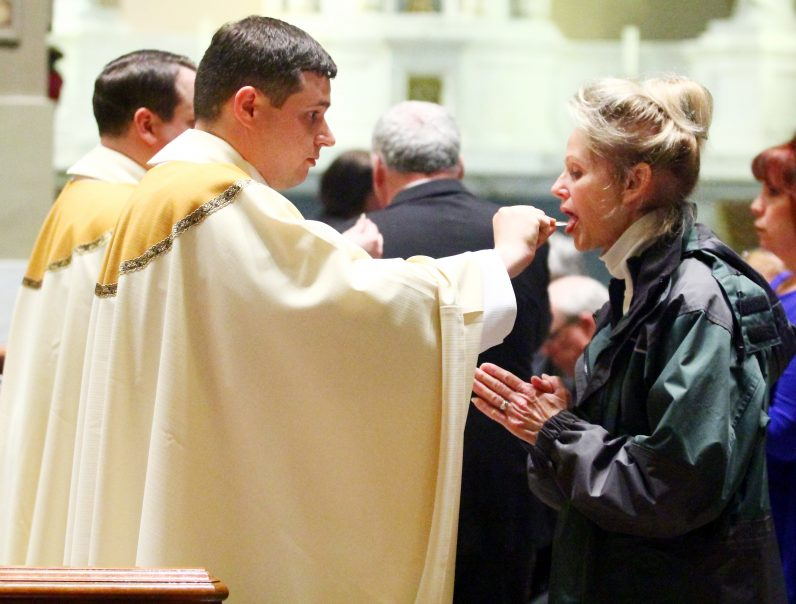 Father Thomas O'Donald distributes holy Communion.