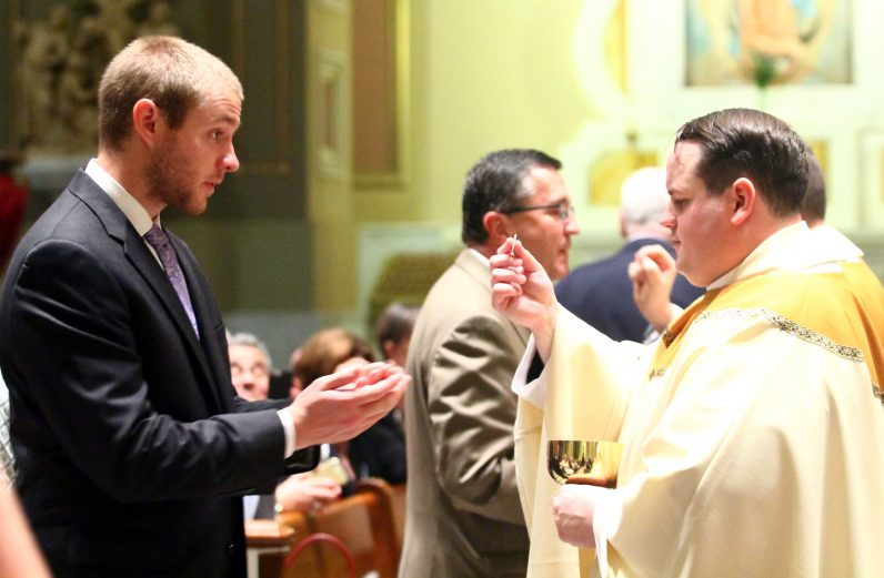 Father Mark Cavara distributes holy Communion.