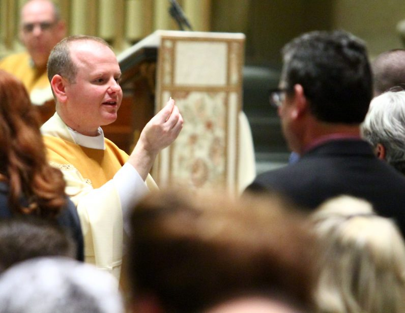 Newly ordained Father Matthew Windle distributes holy Communion at his Mass of ordination.
