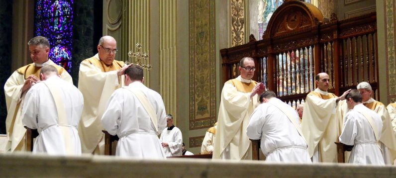 Other priests lay their hands on the heads of the newly ordained priests, strengthening them in their new ministry.