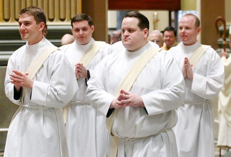 From left, Matthew  Biedrzycki, Thomas O'Donald, Mark Cavara and Matthew Windle process into the Cathedral Basilica of SS. Peter and Paul to be ordained priests.