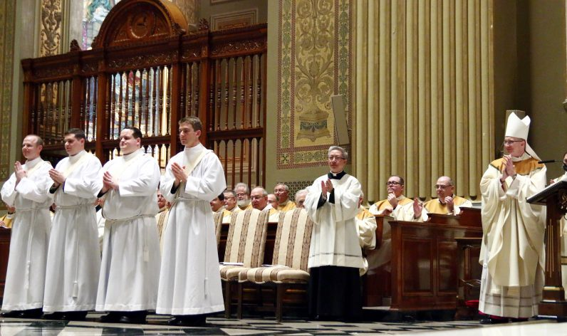 Clergy and all the congregation applaud the determination by Bishop Timothy Senior (right), rector of St. Charles Borromeo Seminary, that the men are worthy to be ordained priests.