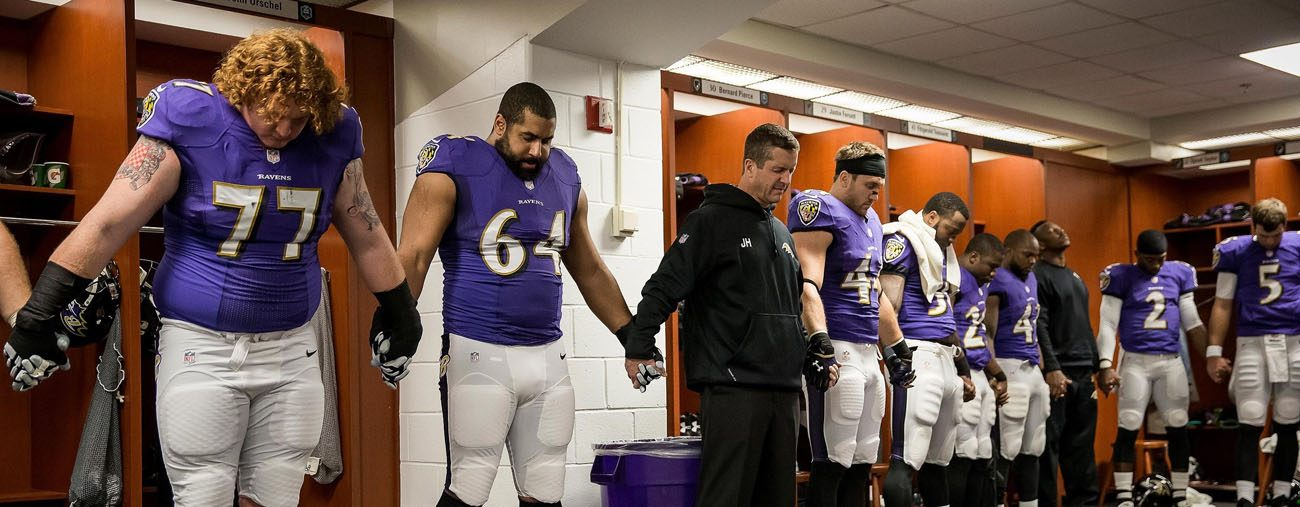 Baltimore Ravens head coach John Harbaugh prays with players after they defeated the Cleveland Browns 20-10 in 2014 at M&T Bank Stadium in Baltimore. (CNS photo/Shawn Hubbard, Baltimore Ravens)